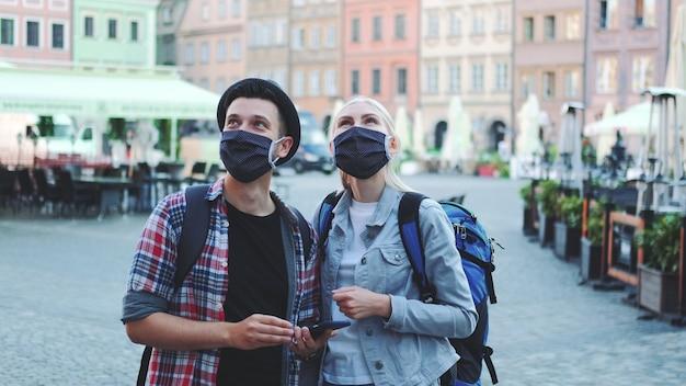 Touristes homme et femme dans des masques de protection et avec des sacs à l'aide de smartphone. ils recherchent des attractions touristiques intéressantes.