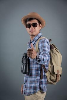 Touristes hommes sac à dos tenant des jumelles fond gris.