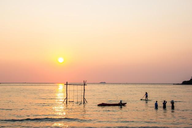 Les touristes jouent dans la mer de l'eau pendant le coucher du soleil dans la région de koh kood trat, thaïlande.