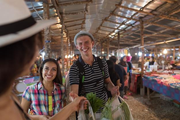 Touristes sur un marché tropical en thaïlande, jeunes achetant des fruits et des légumes frais