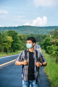 Les touristes masculins portant un masque, portant un sac à dos sur la route.