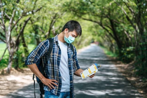 Les touristes masculins se lèvent et regardent la carte sur la route.