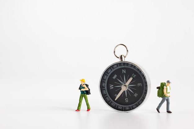 Les touristes miniatures voyagent dans différentes directions avec une boussole sur fond blanc
