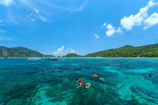 Touristes nageant et faisant de la plongée en apnée dans la mer d'andaman sur les îles phi phi, l'une des plus belles îles de thaïlande