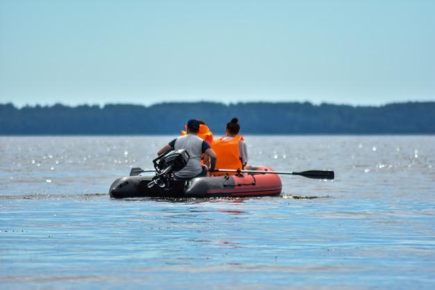 Les touristes nagent sur la rivière en bateau