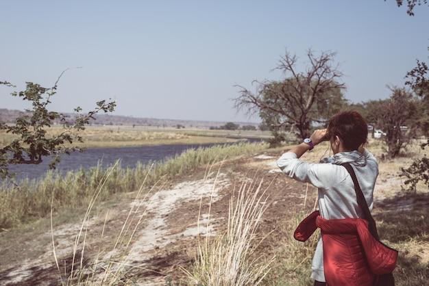 Touristes observant la faune aux jumelles sur la rivière chobe, en namibie, à la frontière du botswana, en afrique.