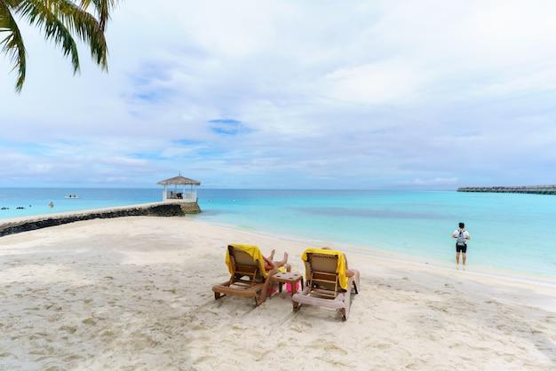 Touristes prenant un bain de soleil et lisant un livre sur la plage de l'île tropicale des maldives