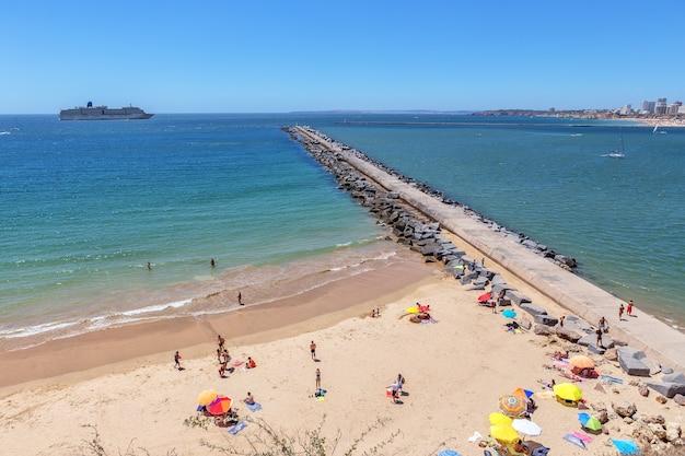 Les touristes prennent le soleil sur la plage à l'entrée de la marina.