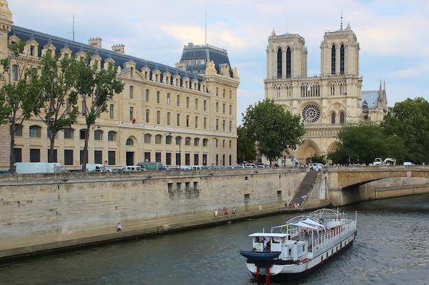 Les touristes profitent d'une excursion en bateau sur la seine près de la cathédrale notre-dame