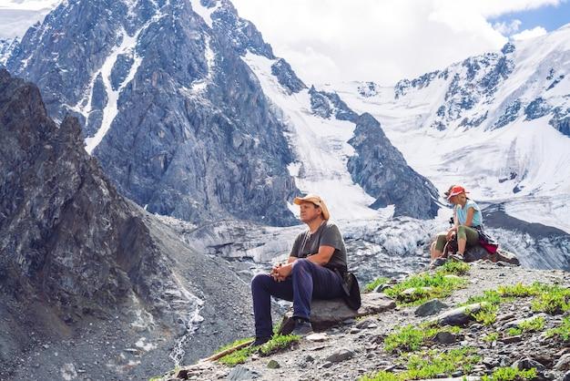 Les touristes s'assoient sur des pierres contre des montagnes enneigées géantes avec des glaciers