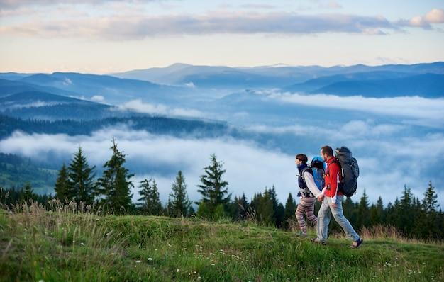 Les touristes avec des sacs à dos marchant le long du chemin de montagne