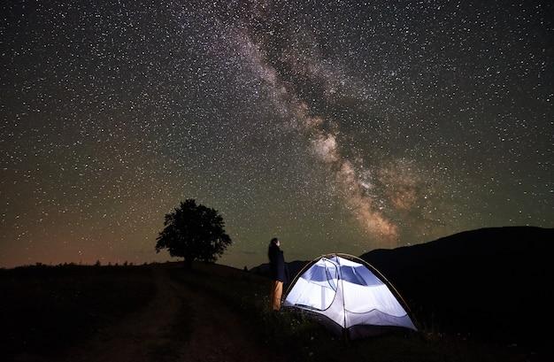 Touristique de femme se reposant la nuit en camping sous le ciel étoilé et la voie lactée