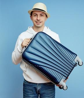Touristique masculin avec une valise dans ses mains, bagage à main d'un touriste