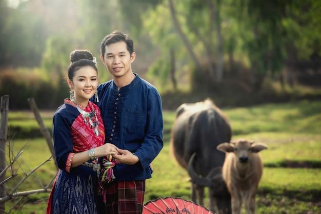 Tournage avant le mariage à l'intérieur du jardin en costumes traditionnels thaïlandais