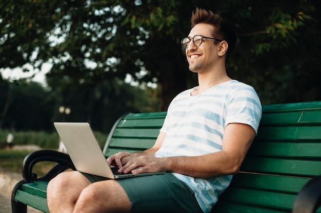 Tournage en extérieur d'un jeune programmeur travaillant sur un banc. portrait de vue latérale d'un jeune étudiant assis avec un ordinateur portable sur ses jambes en souriant.
