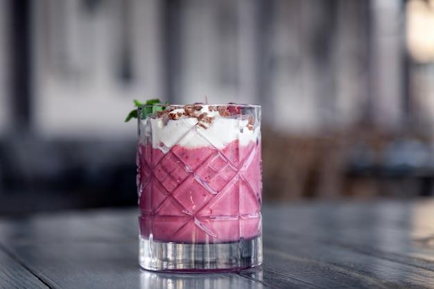 Tournage de nourriture. cocktail de baies en verre de cristal décoré de menthe, baies, grenade, orange, ananas.