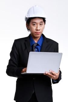 Tournage en studio isolé d'un ingénieur industriel asiatique professionnel de contremaître masculin en costume formel noir et casque de sécurité debout en tapant un rapport sur un ordinateur portable sur fond blanc.