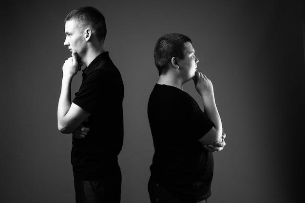 Tournage en studio d'un jeune homme et d'un jeune homme en surpoids ensemble contre un mur noir en noir et blanc