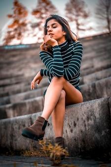 Tournage de style de vie d'automne, une jeune brune aux jambes croisées assis dans l'amphithéâtre de saint-sébastien