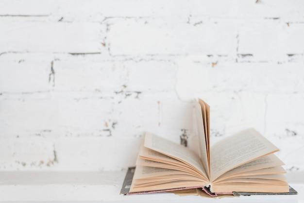 Tournant les pages du livre contre le mur de briques blanches