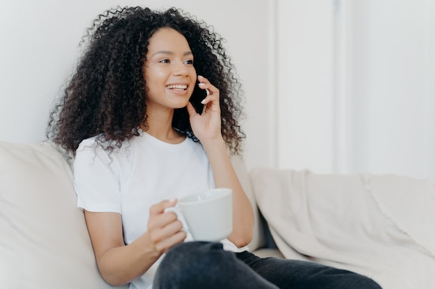 Tourné de côté d'une femme brune ethnique positive a une conversation téléphonique, boit des boissons chaudes