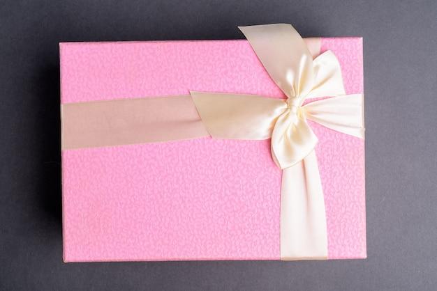 Tourné directement au-dessus de la boîte-cadeau rose sur gris