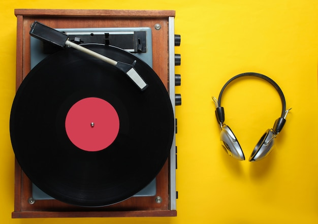 Tourne-disque vinyle rétro, casque sur fond jaune. vue de dessus