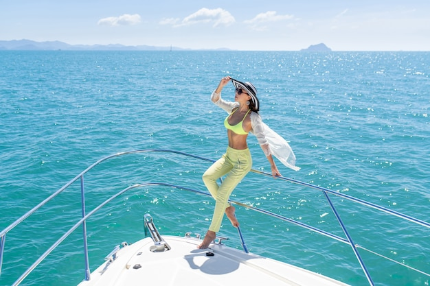 Tourné en plein air de l'adorable jeune femme dans un costume d'été et un chapeau assis sur le bord du yacht