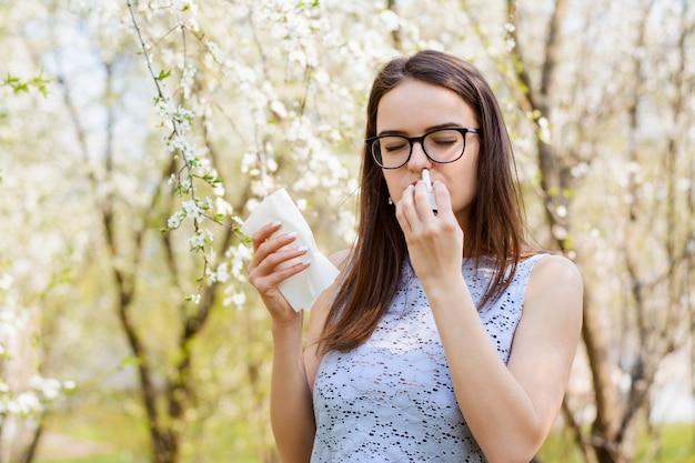 Tourné en plein air de jeune fille contre blooming park à l'aide d'un inhalateur ayant le nez qui coule au printemps