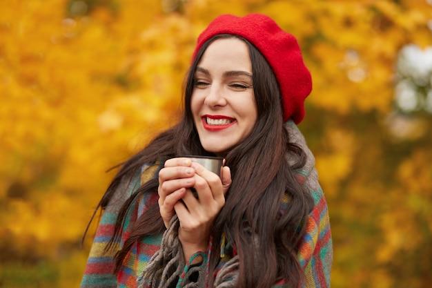 Tourné en plein air de jolie fille avec du café du matin dans une tasse thermos, charmante femme exprimant le bonheur, une couverture à carreaux chaude enveloppée de femmes