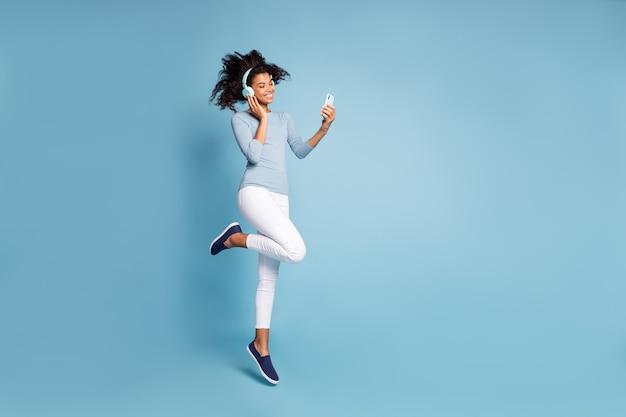 Tourné pleine longueur photo de la taille du corps de joyeux positif mignon jolie jolie petite amie sautant dans un pantalon blanc à l'écoute de la musique isolé couleur pastel fond bleu avec téléphone