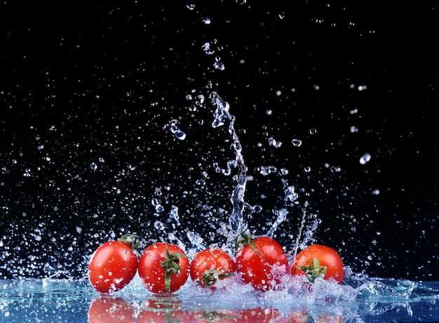 Tourné en studio avec gel de tomates cerises dans les éclaboussures d'eau sur fond noir
