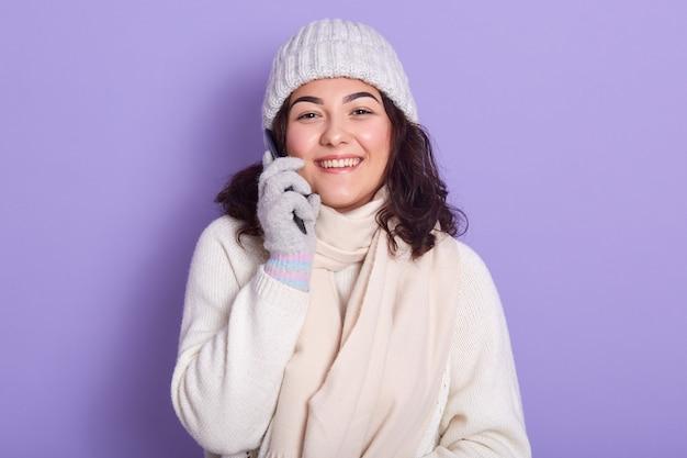 Tourné en studio intérieur de jeune mannequin souriant positif debout isolé sur lilas