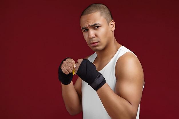 Tourné en studio isolé d'un jeune combattant afrio-américain furieux portant une chemise de sport sans manches blanche et des bandages de boxe noirs, regardant la caméra avec un regard féroce tout en travaillant dans une salle de sport