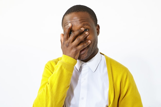 Tourné en studio isolé de séduisant jeune homme afro-américain dans des vêtements élégants couvrant le visage avec la paume, riant de situation ridicule drôle. languette corporelle, expressions humaines, gestes et signes
