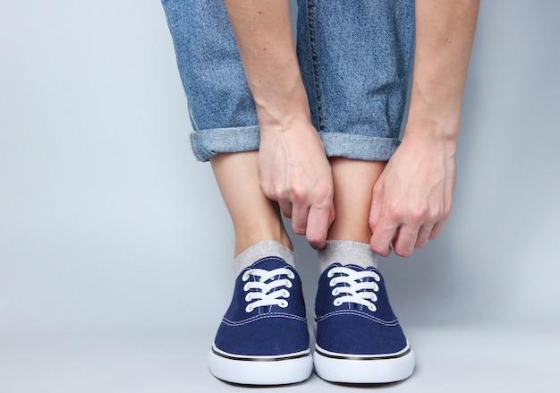 Tourné en studio à la mode. femme en jeans et baskets apparaît une chaussette sur gris.