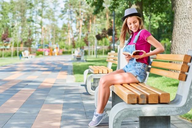 Tourné sur toute la longueur d'une belle jeune femme appréciant la lecture d'un livre dans le parc local assis sur le banc sur une chaude journée ensoleillée copyspace loisirs étudiant en littérature étudiant concept.