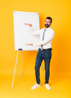 Tourné sur toute la longueur de l'homme d'affaires donnant une présentation sur un tableau blanc sur fond jaune isolé holding pour insérer une annonce