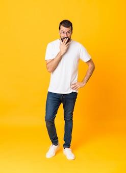 Tourné sur toute la longueur de l'homme à la barbe sur jaune isolé avec des lunettes et surpris