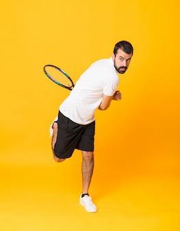 Tourné sur toute la longueur de l'homme jouant au tennis sur jaune isolé