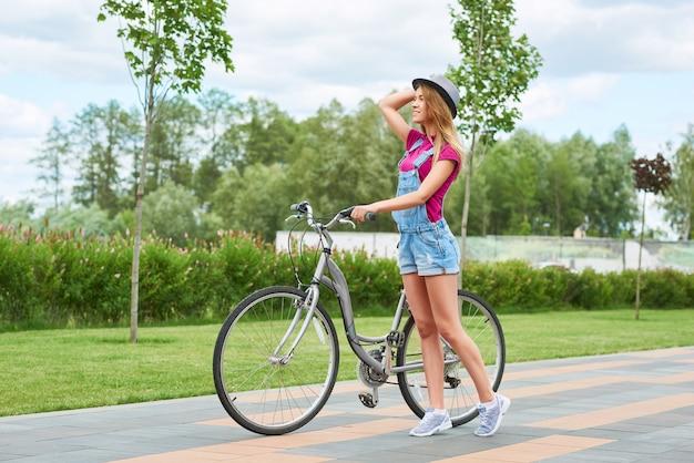 Tourné sur toute la longueur d'une jeune femme marchant dans le parc avec son vélo nature loisirs en plein air été cycliste saisonnier équitation concept d'activité sportive.