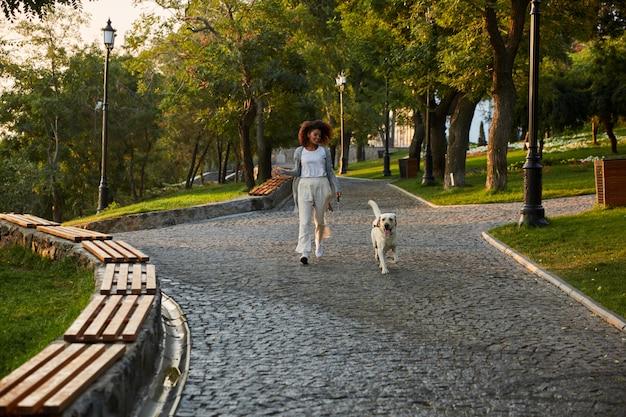 Tourné sur toute la longueur d'une jolie jeune femme en bonne santé marchant le matin dans le parc avec un chien