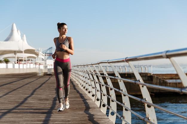 Tourné sur toute la longueur de la jolie jeune femme qui court le long de la promenade du bord de mer vers la caméra