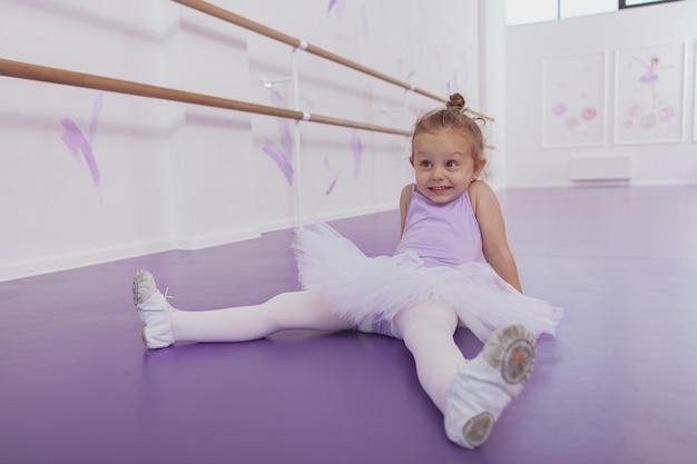 Tourné sur toute la longueur d'une mignonne petite ballerine heureuse souriant joyeusement, assis détendu à l'école de ballet sur le sol