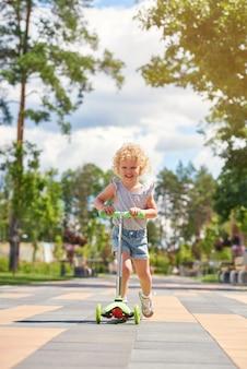 Tourné sur toute la longueur verticale d'une jolie petite fille blonde équitation scooter au parc enfants enfants bonheur émotions concept d'activité.