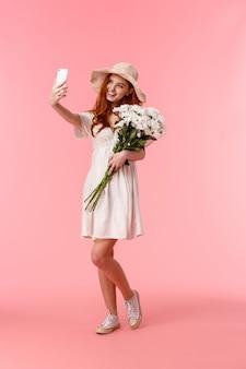 Tourné vertical sur toute la longueur belle, romantique et idiote femme rousse appréciant la belle journée de printemps, tenant des fleurs bouquet et prenant selfie sur smartphone, souriant ravi