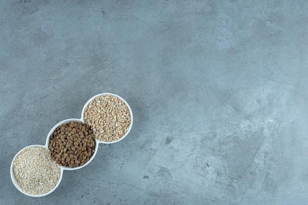 Tournesol, graines de citrouille et grains de riz dans des tasses blanches. photo de haute qualité