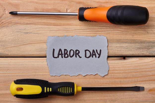 Tournevis et carte sur bois. papier de voeux pour la fête du travail. célébrer les droits des travailleurs.