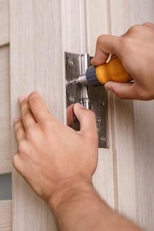 Le tournevis installe la vis sur les charnières de porte en acier inoxydable avec porte battante en bois