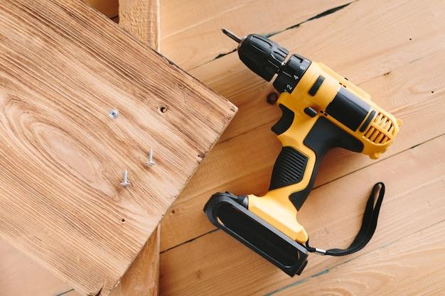 Tournevis jaune sur une table en bois. perceuse électrique